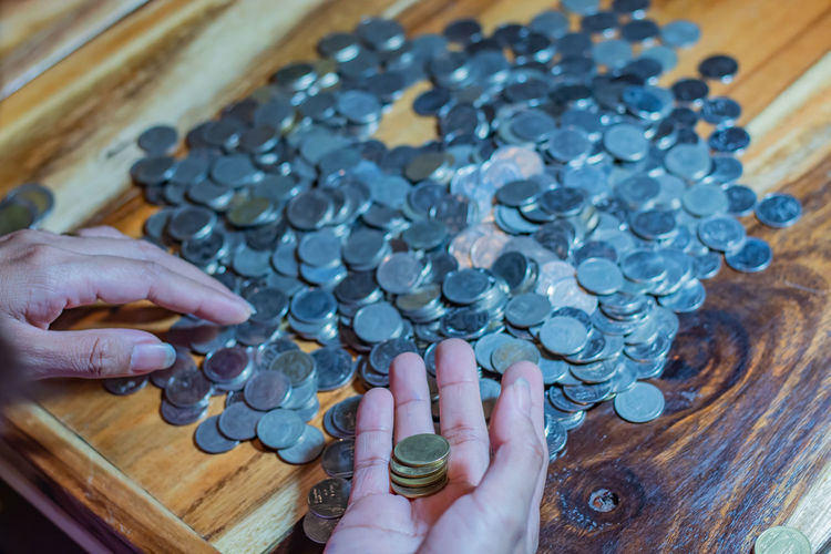 Cropped hands of woman counting coins on table