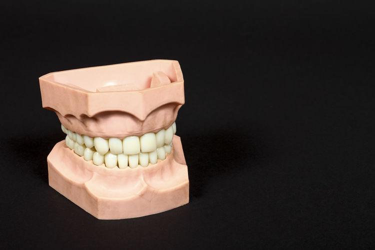 Close-up of dentures against black background