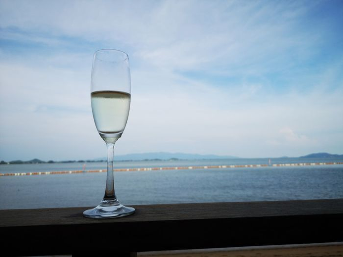 Glass of water on table by sea against sky