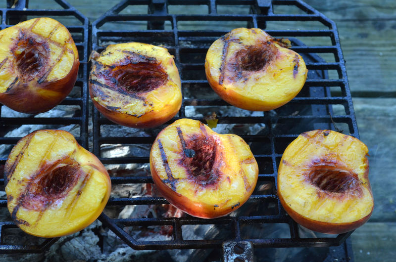 Peach halves grilling on top of a small tabletop Hibachi grill on picnic table outdoors Barbecue Close-up Day Food Food And Drink Freshness Grill Grilled Peaches Hibachi Grill In A Row Indulgence No People Peach Peach Halves Peaches Ready-to-eat Temptation Yellow