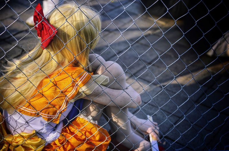 Girl sitting by chainlink fence