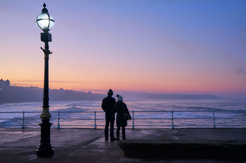 Couple Standing Together Looking Out To Sea At Sunset Adult Adults Only Ambient Light Beanie Blue Cloud - Sky Cold Weather Full Length Glowing Lights Lamp Post Orange Outdoors Railing Sea And Sky Sea Froth Silhouette Sky Soft Light Standing Street Light Sunset Water Waves Breaking On A Shore Waves Rolling In Wooly Hat