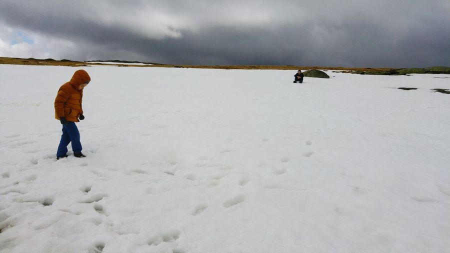 Full Length Of Child Walking On Snow Covered Field Against Sky