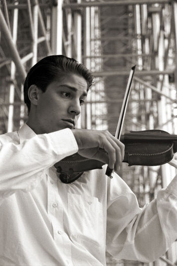 Man playing violin while standing against scaffolding