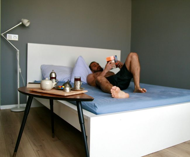 Man reading book while lying on bed at home