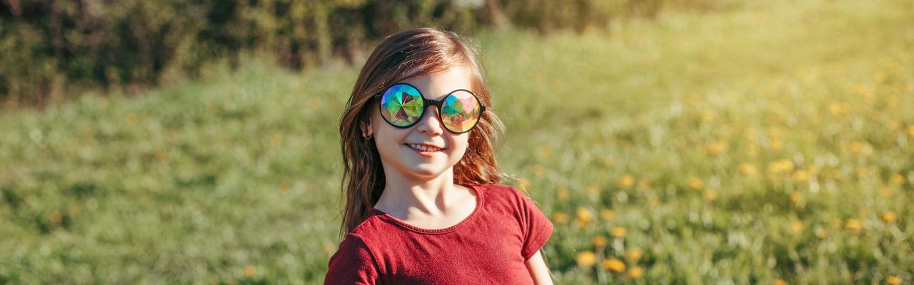 Portrait of girl wearing sunglasses on field