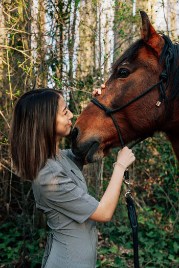 Smiling woman standing by horse against trees