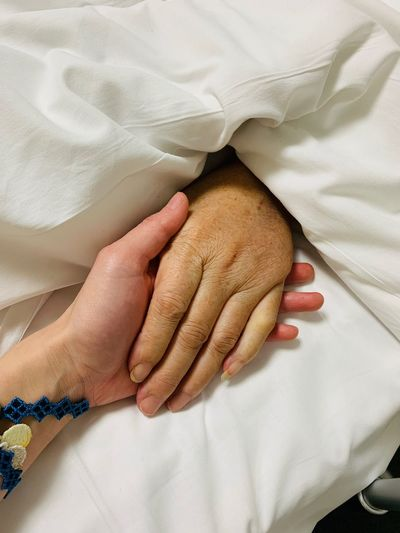 Cropped image of people holding hands on bed at hospital