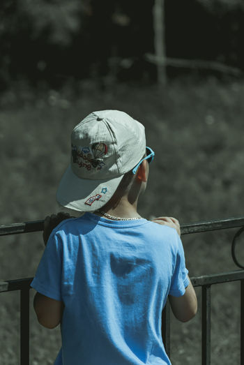 Rear view of boy wearing cap while leaning on railing