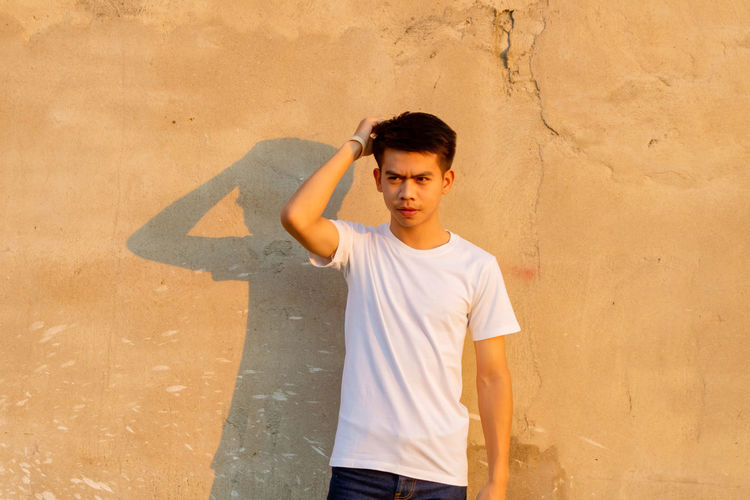Thoughtful young man looking away against wall