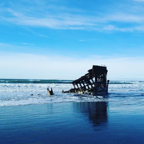 Destroyed Pier In SEA AGAINST CLOUDY SKY