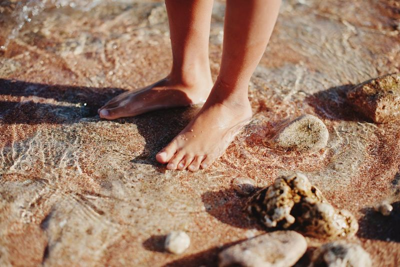 Low section of child standing on sand