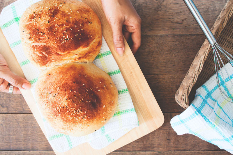 Hands holding a plate of homemade breads on wood background Adult Bake Bakery Bakery Cafe Bakery Shop Bakerylove Bread Breakfast Cafe Cafe Time Chef Close-up Coffee Break Day Human Body Part Human Hand Indoors  One Person One Woman Only Only Women People Student Touching