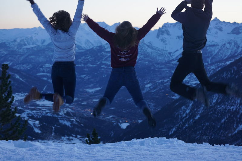 Mountain Walking Arms Raised Cold Temperature Emotion Enjoyment Excitement Freedom Friendship Full Length Fun Human Arm Jumping Leisure Activity Lifestyles Limb Mid-air Outdoors People Positive Emotion Real People Rear View Snow Togetherness Two People Warm Clothing Winter
