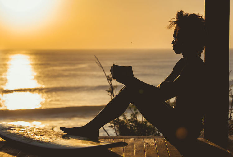 Side view of silhouette woman holding book against sea sky during sunset
