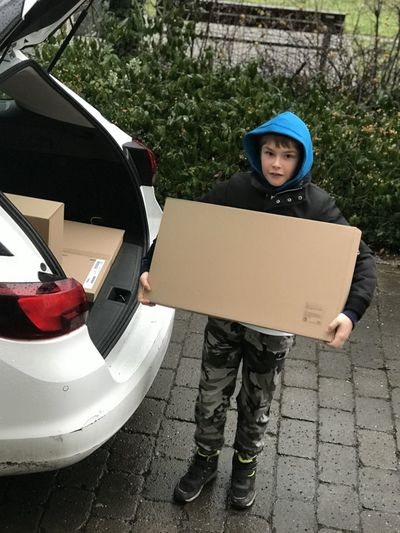 Portrait of a boy holding a car