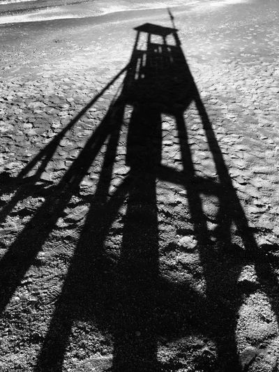 Shadow of person on sand at beach