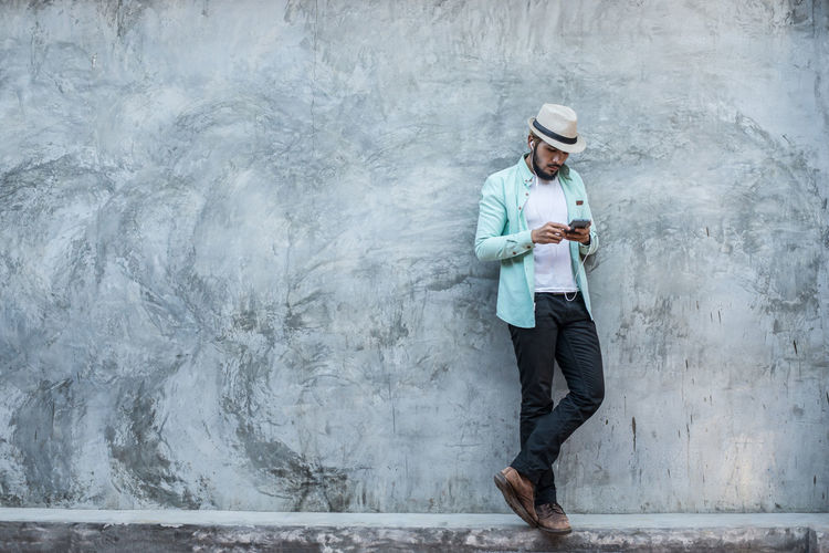 Man using phone while standing against gray wall