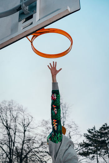 Low angle view of person with arm raised by basketball hoop against sky
