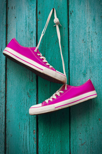 Pink shoes hanging on wooden wall