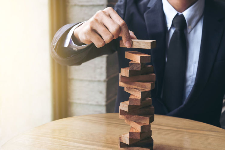 Midsection Of Businessman Stacking Wooden Blocks On Table