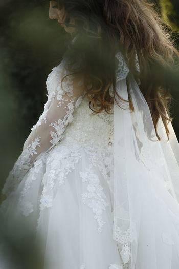 Midsection of bride standing outdoors