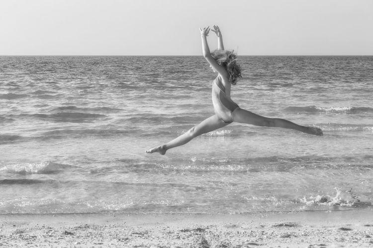 Full length of woman dancing at beach against sky