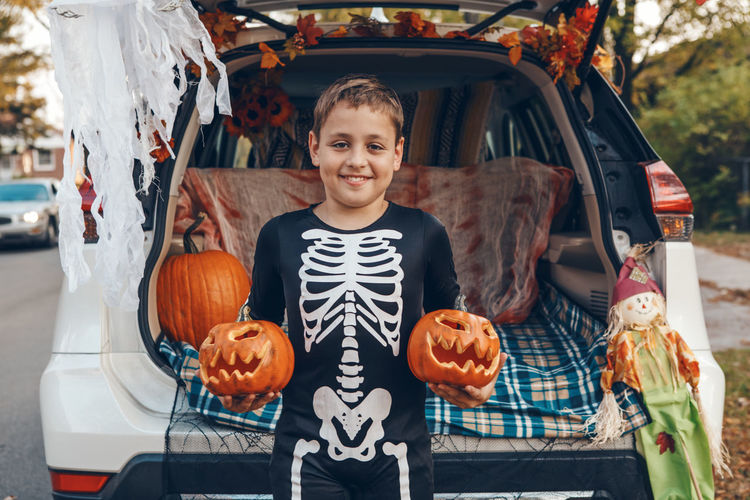 Portrait of smiling boy with pumpkins in market