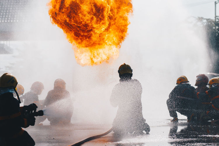 Firefighters training , fireman Burning Communication Day Fire Fire - Natural Phenomenon Fire Hose Flame Group Of People Heat - Temperature Medium Group Of People Men Motion Nature Orange Color Outdoors People Real People Rear View Smoke - Physical Structure Spraying Water