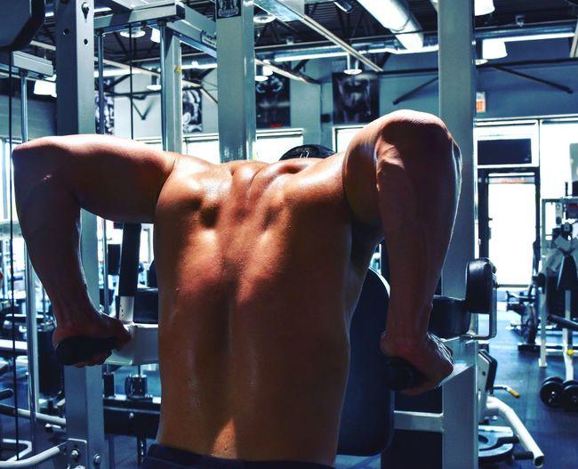 Rear View Of Shirtless Muscular Man Exercising In Gym