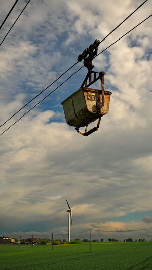 Low angle view of overhead cable cars on field against sky