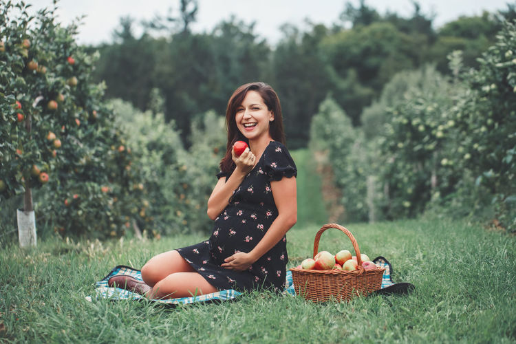 Young woman smiling while sitting on grass in field