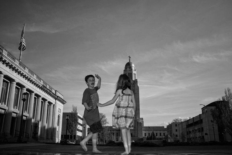 Girl And Boy Standing Against Nebraska State Capitol Building