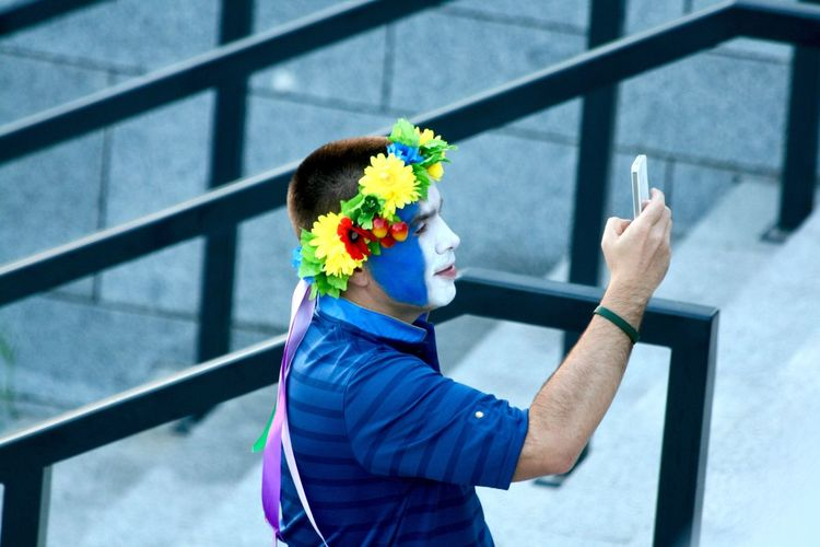 Side view of man with painted face wearing flowers taking selfie through mobile phone