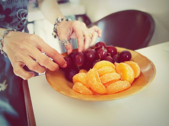 Cropped hand of woman arranging fruits in plate at table