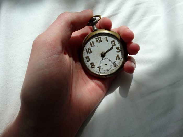 Cropped hand holding old pocket watch on bed