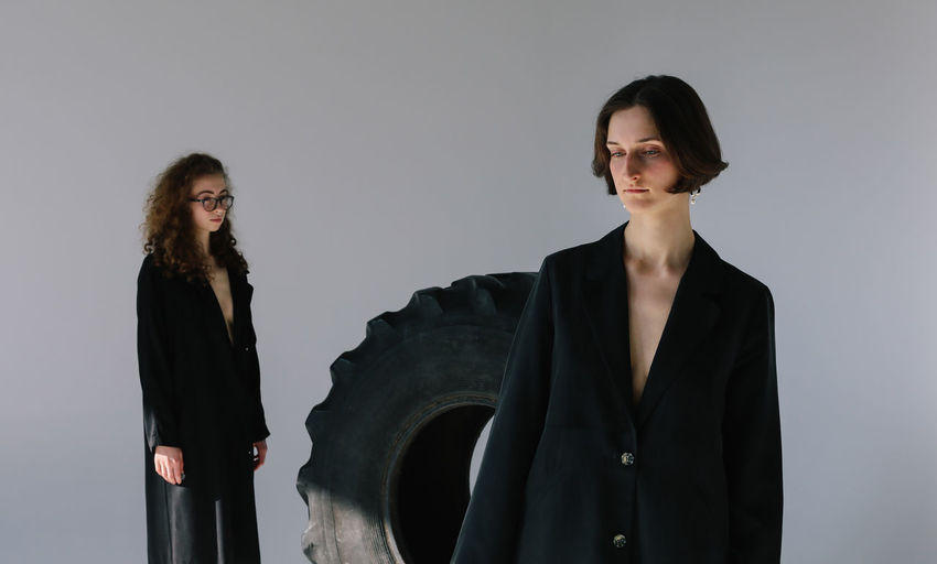 Standing Studio Shot Women Young Adult Black Color Indoors  Females Hairstyle Portrait Clothing Young Women Front View Two People Gray Background Fashion People Contemplation Looking At Camera Portrait Of A Woman Girls Tire Black Thoughtful Females Gray Fashion Photography Style Stylish