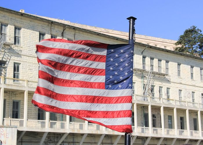 Close-up of american flag against building on sunny day