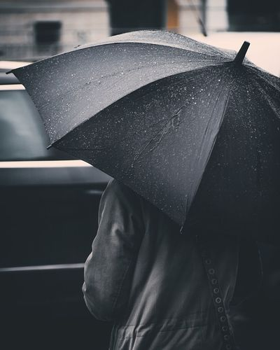 Rear view of person holding wet umbrella during monsoon