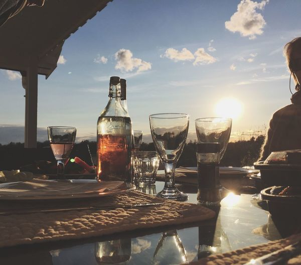 Wine bottles and glasses against cloudy sky