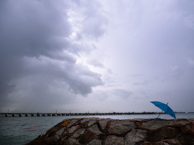 Blue umbrella on groyne under cloudy sky Cloud - Sky Sky Water Sea Beach Tranquility No People Outdoors Umbrella Blue Groyne Groin Rain Dramatic Clouds Weather East Coast Park Jetty