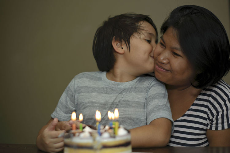 Close-up of son kissing mother during birthday