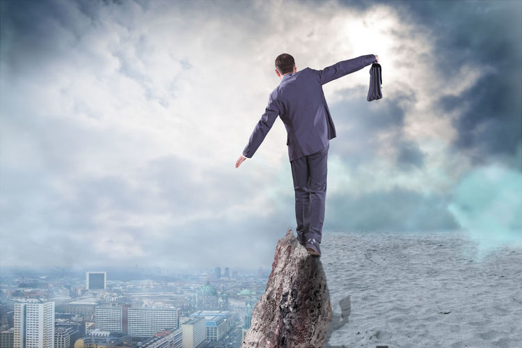 Digital Composite Image Of Man Walking On Cliff Against Cityscape