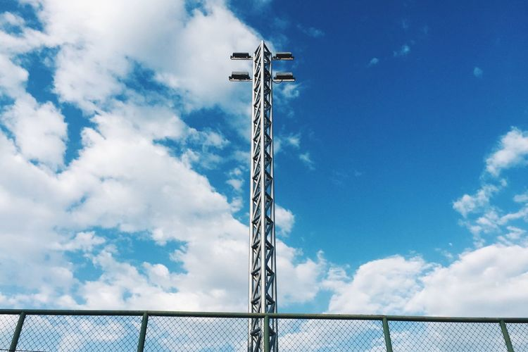 Low Angle View Of Floodlight And Chainlink Fence Against Sky