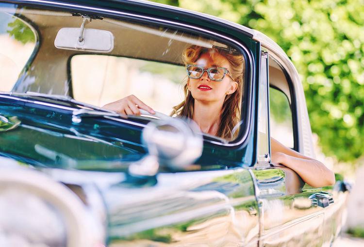 Smiling woman driving vintage car