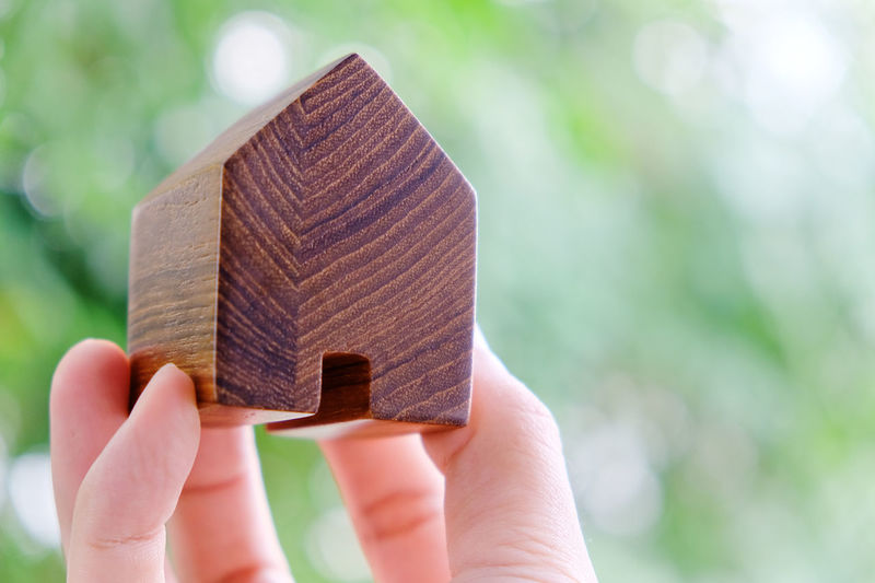 Cropped hand holding wooden model home