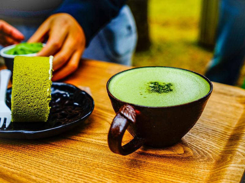 Green tea roll cake and green tea latte coffee in green tea shop at Osulloc tea museum, Jeju island, South Korea. Osulloc Bowl Close-up Day Drink Focus On Foreground Food Food And Drink Freshness Frothy Drink Green Color Green Tea Healthy Eating Human Hand Indoors  Matcha Tea One Person People Plate Ready-to-eat Real People Refreshment Sitting Table Tea - Hot Drink