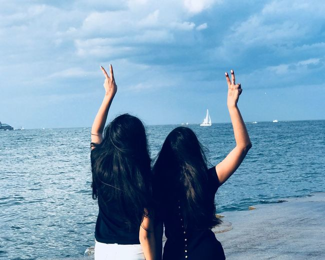 Rear view of female friends gesturing while standing by sea