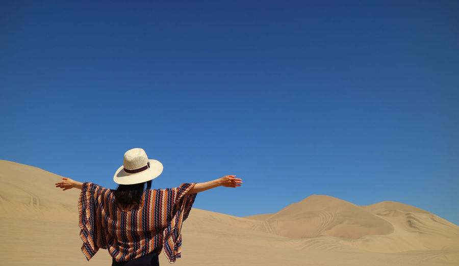 Rear view of woman on desert against clear blue sky