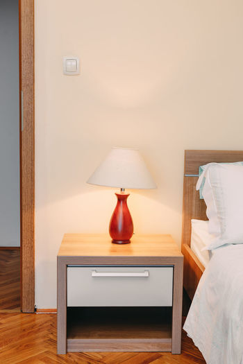Illuminated lamp on table by wall at home